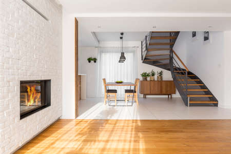Modern, white apartment with fireplace, table and staircase