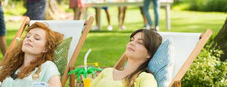 Relaxed girls are sunbathing on the sunbeds in garden