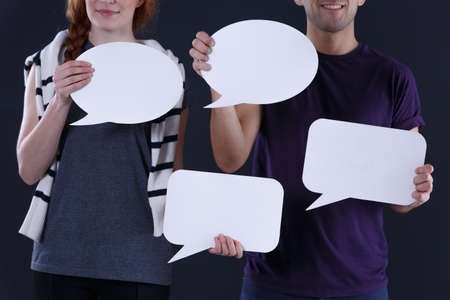 empty of people: Young people smiling and holding empty speech bubbles in front of them