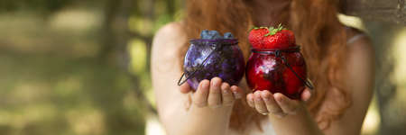 Closer shot of two jars with seasonal fruits kept by young girl