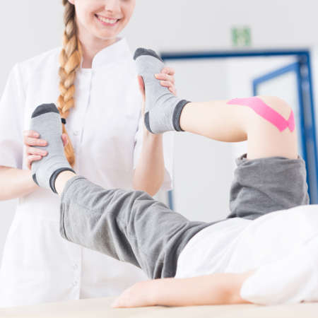 Young professional physiotherapist exercising with patient during rehabilitation