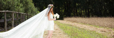 Young bride with long, white veil standing in the country area