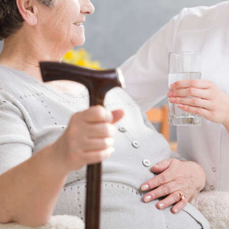 Elderly disabled woman with a walking stick and carer giving her glass of water Stock Photo