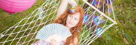 Girl lying on a hammock with the soap bubbles floating in the air