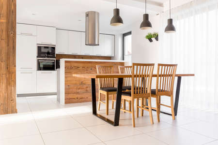 kitchen furniture: New white kitchen with wood table, chairs and island Stock Photo