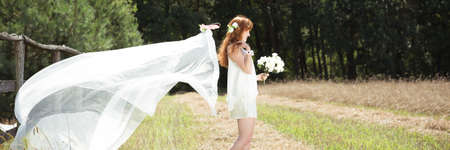 Woman in white wedding dress keeping the bunch of flowers in natural scenery