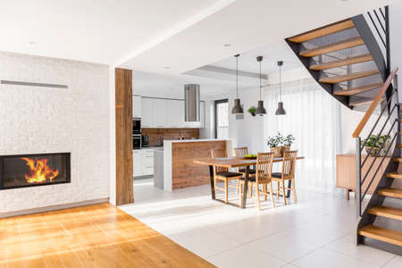 Modern luxury open plan apartment with stairs, communal table, kitchen