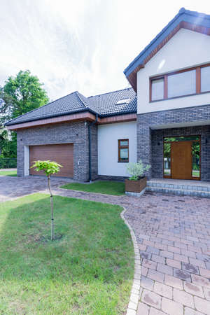 Suburban detached house with cobbled frontyard and driveway to the garage Stock Photo