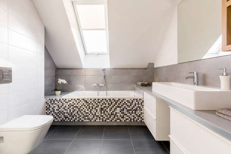 Grey and white bathroom with washbasin, toilet and bathtub