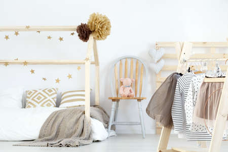 Bed and girls clothes in cozy stylish room Stock Photo