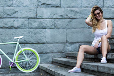 Shot of a happy young woman sitting on the stairs with a bicycle in the background