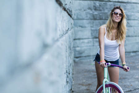 Happy woman wearing sunglasses and riding her bicycle