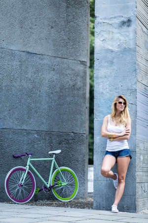 Shot of a fit girl leaning against the wall with hipster bicycle in the background