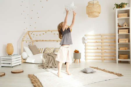 Little girl playing in a cozy modern bedroom 스톡 콘텐츠