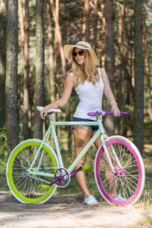 Beautiful girl standing with colourful bicycle in the woods