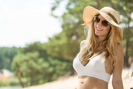 Cropped shot of a smiling woman wearing a white bikini top and a hat