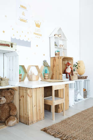Wooden desk in cozy kids room with toys