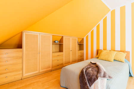 Attic bedroom with intense yellow walls and fitted wardrobe