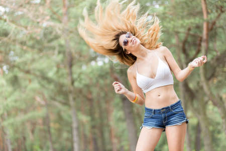 Young happy girl jumping up in the air in a forest