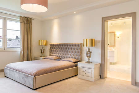 luxury house: Shot of a luxurious bedroom interior with a large bed, designed in bright tones