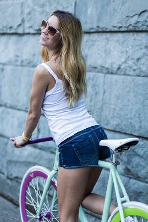 Blonde young woman in sunglasses riding on her stylish bicycle