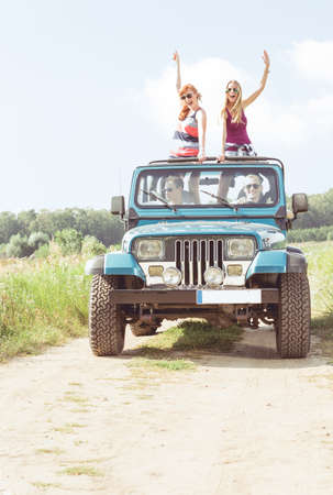 Girls in off-road vehicle during summer day