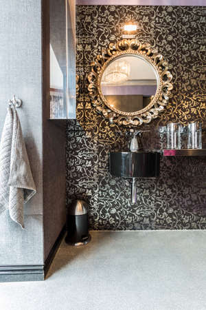 bathroom mirror: New bathroom with pattern wallpaper, sparkle floor, round mirror with decorative golden frame and black basin
