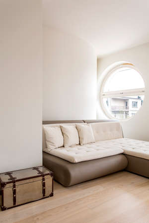 Shot of a minimalistic interior with a sleeper sectional and a circular window Stock Photo