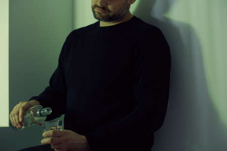 Depressed man pouring himself a glass of vodka at night
