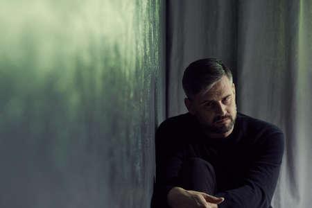 夜に灰色の壁の隣に座って思慮深い中年男