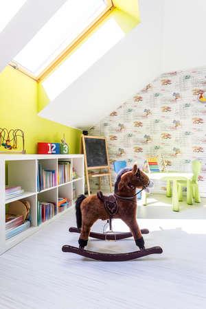 中心部に茶色のロッキング馬とかわいい子供部屋 写真素材