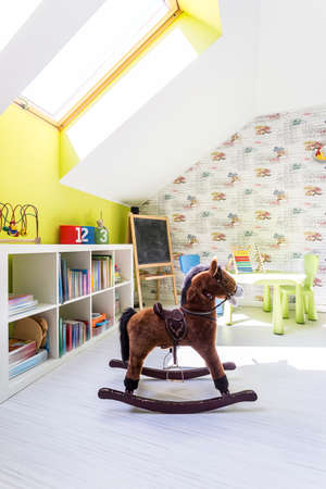 Cute kids room with a brown rocking horse in the centre