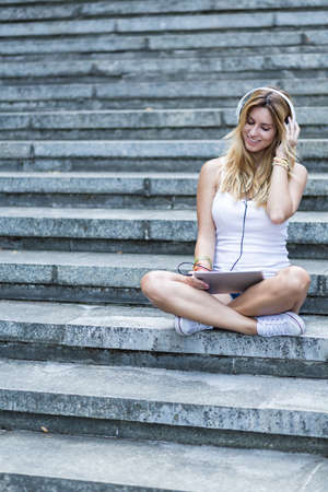Shot of a woman sitting on the stairs with a digital tablet and listening to the music