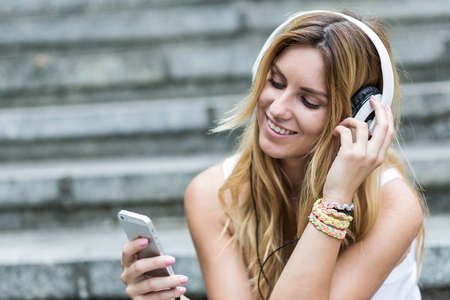 Cropped shot of a smiling girl wearing headphones and looking at her mobile phone