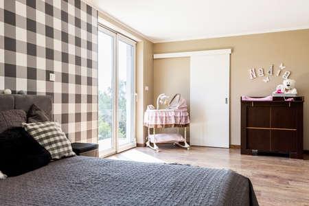 Beige bedroom with a newborns corner with crib on wheels