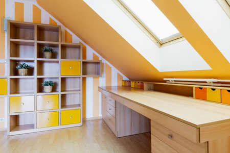 Yellow office room in an attic, with a set of shelves and a long wooden desk Imagens