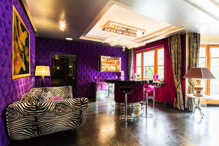 Modern living room with violet upholstered walls, glitter floor, pattern zebra sofa, bar table and stools