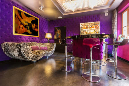 stool: Spacious villa interior with upholstered violet walls, double zebra pattern sofa, bar table and two stools