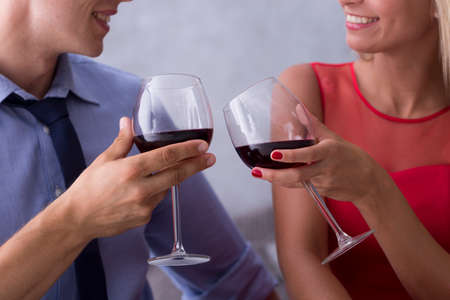 Close-up of young couple celebrating with red wine
