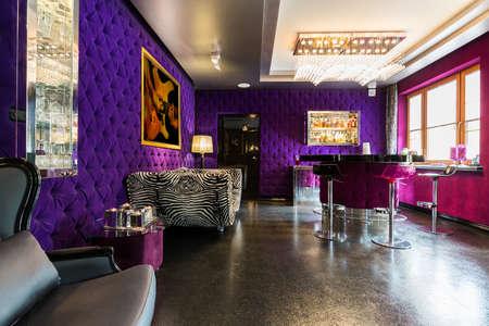 Appartement design moderne avec murs violet rembourrés, sol scintillant, bar et canapé à motif zèbre Banque d'images - 77959079
