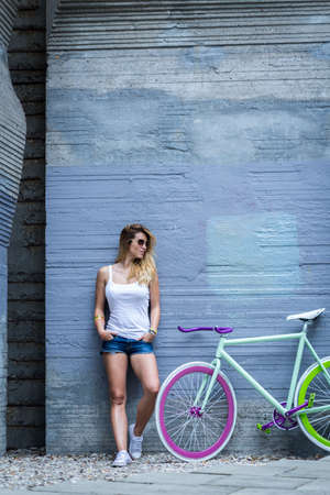 Shot of a young fit girl wearing white top, standing next to her bicycle