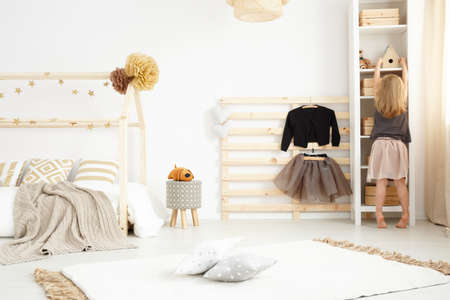 Meisje het spelen in haar beige en witte moderne slaapkamer