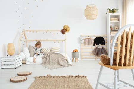 Meisje zit op haar bed in witte Scandinavische slaapkamer