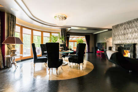 luxury house: Modern villa interior with sparkle floor, fireplace, window wall, round glass table and black upholstered chairs