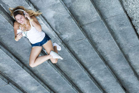 Shot of a young girl lying on the steps and listening to the music Stock Photo