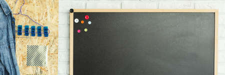Blackboard with colorful bottons hanging on white brick wall, panorama