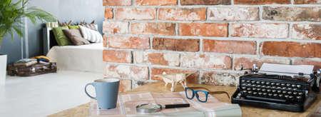 oficina en casa con pared de ladrillo, máquina de escribir sobre el escritorio, panorama