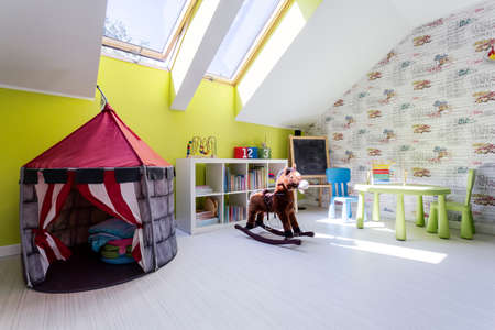 Optimistic kids room with play tent and a rocking horse