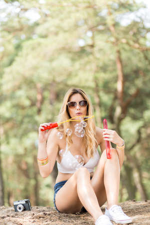 Shot of a beautiful girl sitting on the hilltop and blowing bubbles in the air Stock Photo