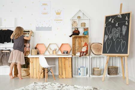 Meisje in een moderne kamer met speelgoed en houten meubels